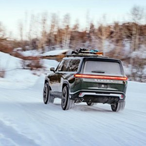 2020 Rivian R1S rear shot driving through snow path