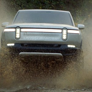 2020 Rivian R1T front shot driving through mud and water